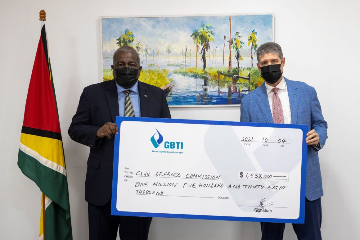 GBTI CEO (ag) James Foster presents the symbolic cheque to Prime Minister Honourable Brigadier (Ret'd) Mark Phillips